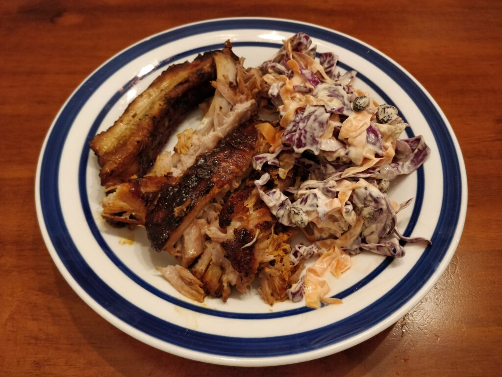 Slow-cooked BBQ pork ribs sliced into individual ribs served with red cabbage slaw.
